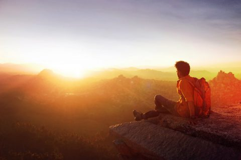 man-sitting-on-edge-facing-sunset-915972