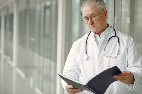 contemplative-doctor-in-uniform-reading-clinical-records-4173239