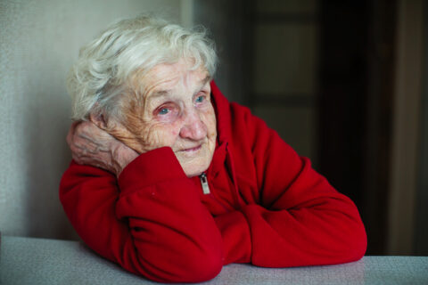 Very old woman pensioner in her house, a portrait sitting at a table in a red jacket.